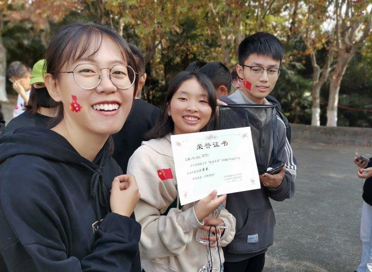 图为参赛同学展示获得奖状与环保物资 张倩钰 摄.jpg